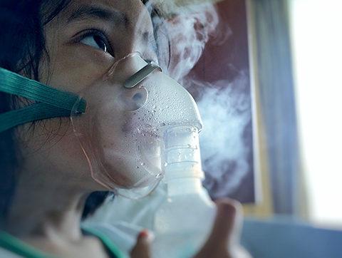Girl with a nebulizer inhaling aerosolized medicine