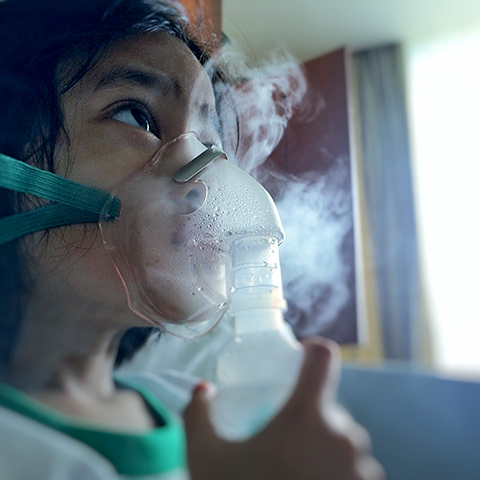 Girl with a nebulizer inhaling aerosolized medicine