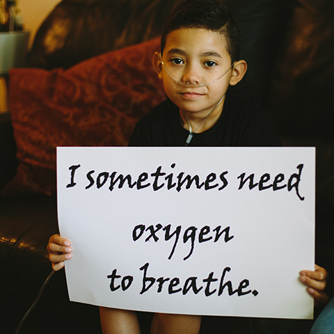 A boy with oxygen supply tube holding a sign saying